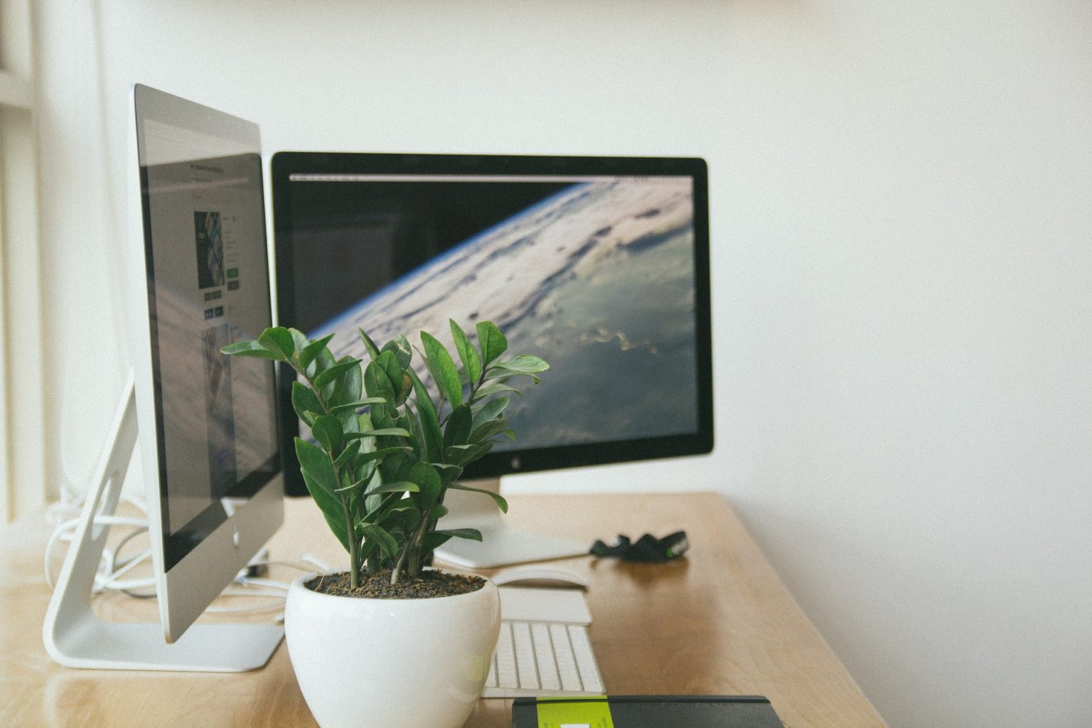 Apple iMac sitting on desk with green plant