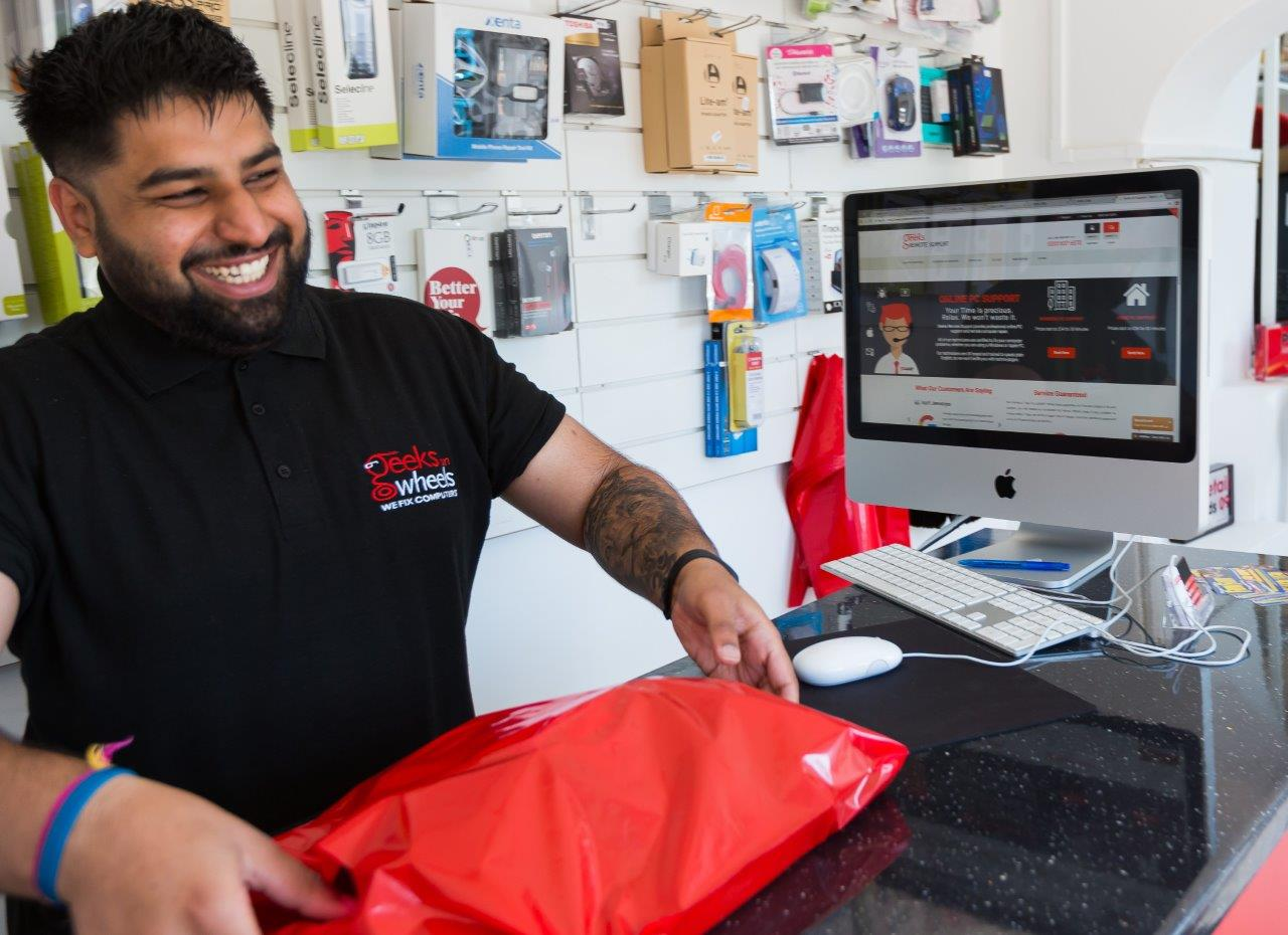 Geeks On Wheels staff member serving customers with red bag and iMac