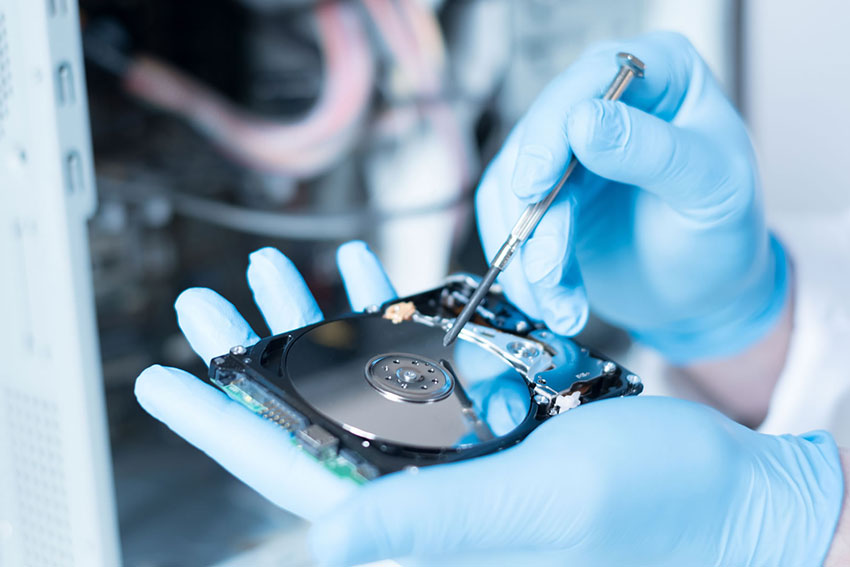 Fixing a hard drive with blue gloves and a screwdriver