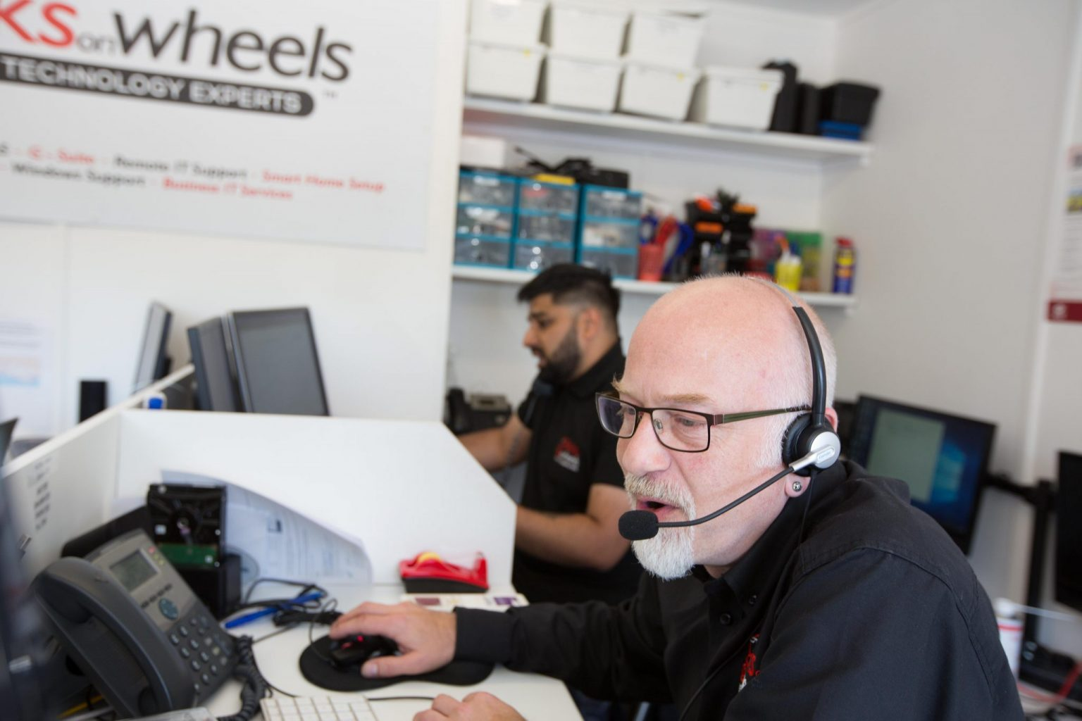 Geeks On Wheels team member speaking to a customer remotely using a headset